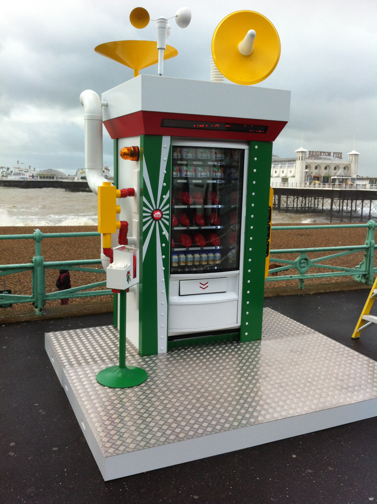 A Kellogg Cornflake vending machine by the sea, a pier in the background