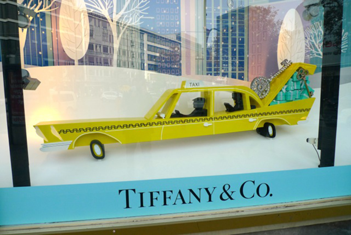 A Tiffany Christmas window display, a car, packed with gifts in a snowy street scene